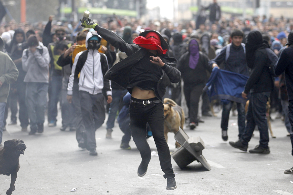 A student protester prepares to throw a bottle with paint at riot police officers during a rally in which demonstrators demanded that the government make changes to the public state education system, in Santiago April 11, 2013. Chilean students and t